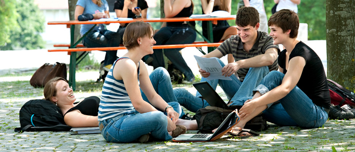 Students with a laptop on the green campus in Freising.